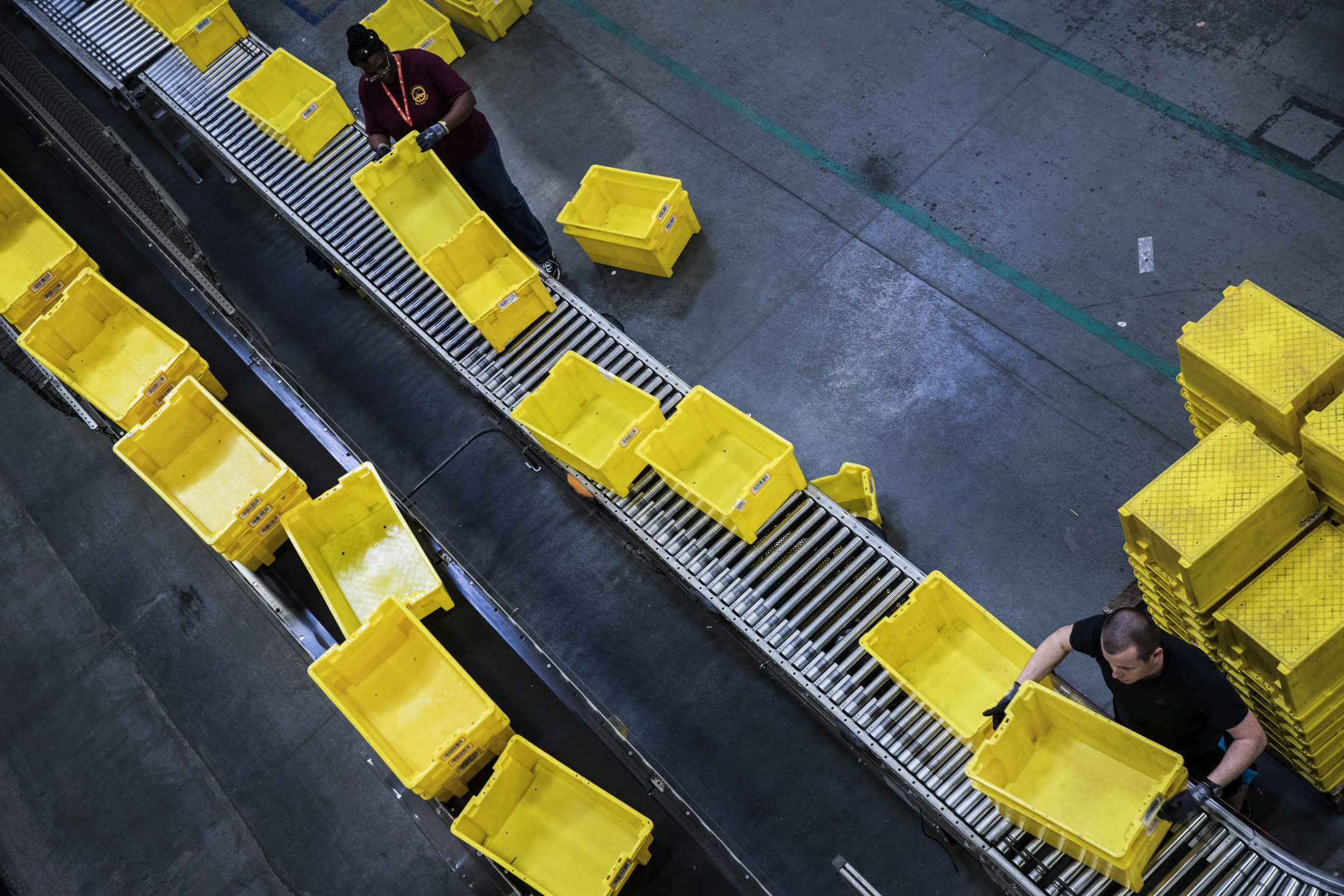 Employees organize plastic bins for orders at the Amazon.com Inc. fulfillment center in Robbinsville, New Jersey, U.S., on Monday, Nov. 27, 2017. The holiday shopping season is off to a strong start and retailers appear to be continuing the momentum today --CyberMonday-- the biggest online spending day of the year. Photographer: Victor J. Blue/Bloomberg via Getty Images