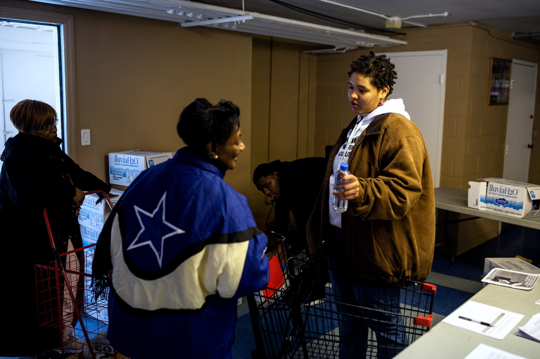 NEWARK, NJ. - FEBRUARY 22, 2020: Aka Awakening explains to a local resident that a new shipment of water will be delivered soon at St. Lucy's Rectory Church in Newark, NJ.