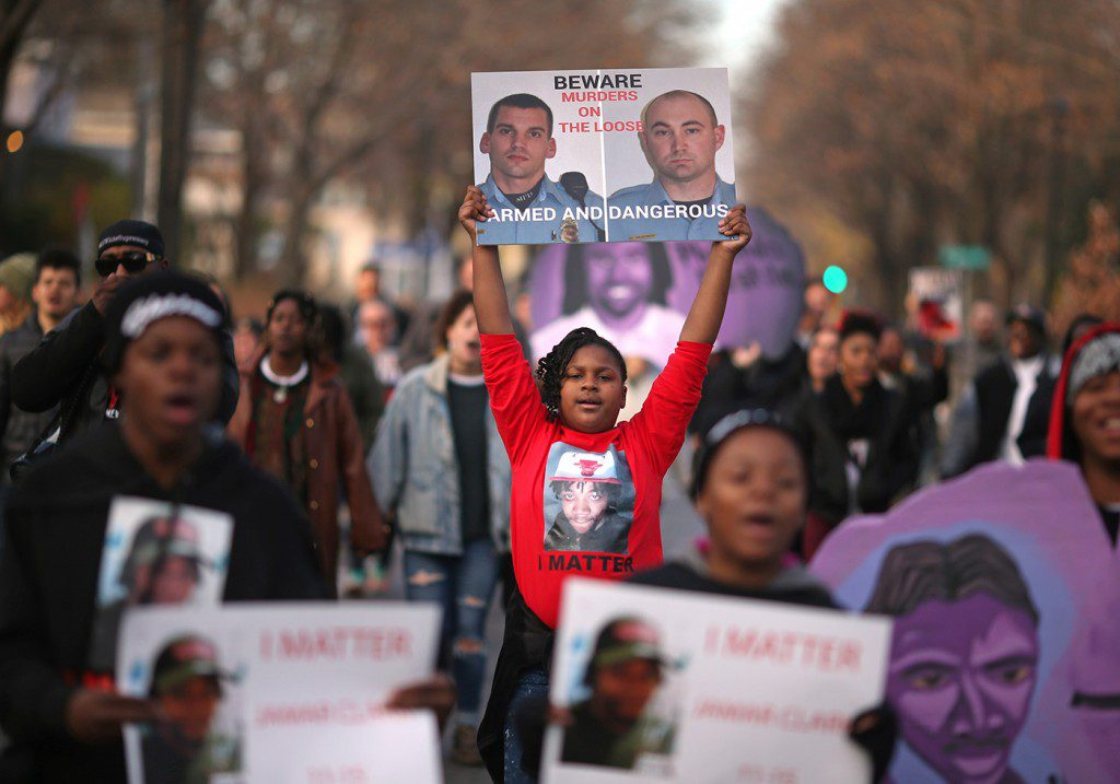 A niece of Jamar Clark protested with a photograph of the two Minneapolis Police that were involved in Clark's death. Family members, friends and activists marched too the spot where Jamar Clark was killed in a confrontation with city police last fall to commemorate his death Tuesday October 15, 2016 in Minneapolis, MN.]  Jerry Holt / jerry. Holt@Startribune.com(Photo By Jerry Holt/Star Tribune via Getty Images)