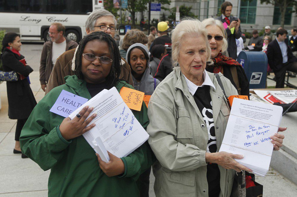 Rev. Yvonne McJetters, left, and Sarah Huffman carry copies of a petition with 4,000 signatures to Speaker Thom Tillis and President Pro Tem Phil Berger's offices at the North Carolina General Assembly building in Raleigh, N.C.  on Monday, April 23, 2012. A coalition of political watchdog groups gathered for the second