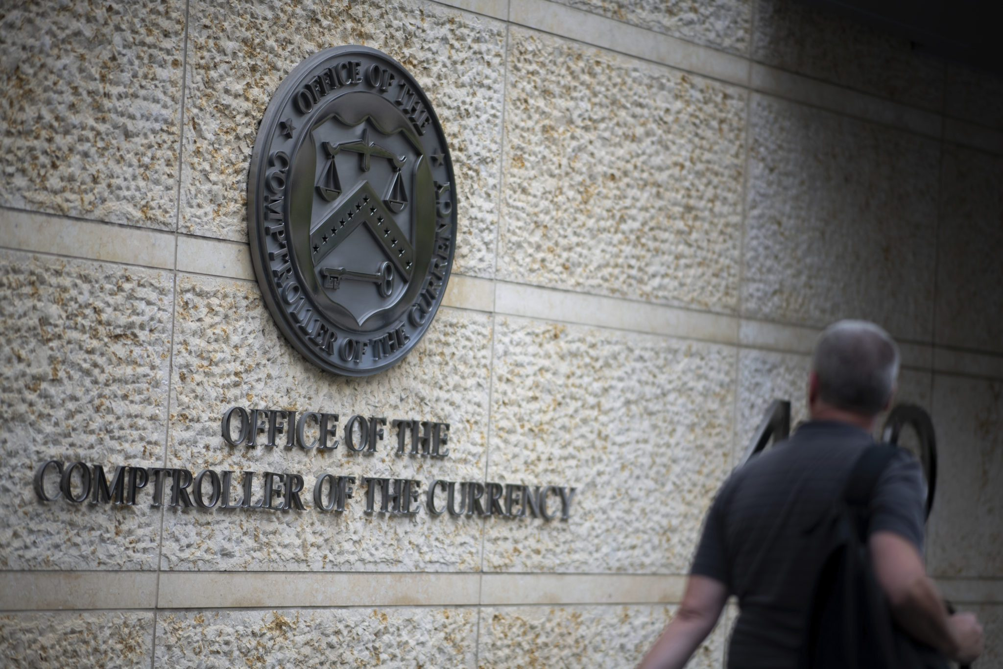 A man walks by the Office of the Comptroller of the Currency logo as it appears on OCC headquarters in Washington, D.C., as seen on September 9, 2019.