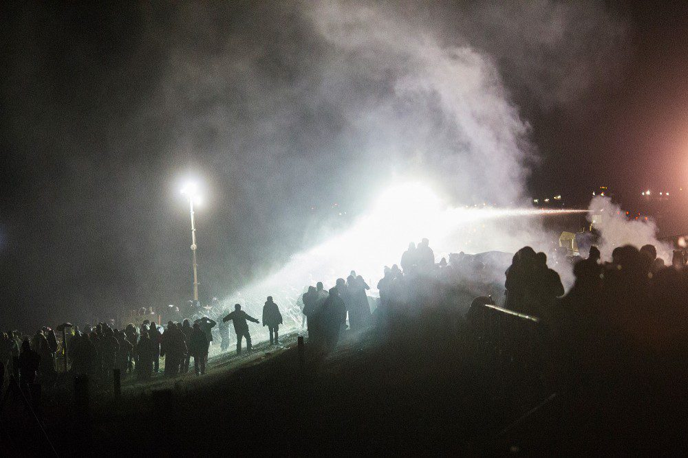 Dakota Access protestors stand their ground on the bridge between Oceti Sakowin Camp and County Road 134 in North Dakota on Sunday, Nov. 20, 2016 while being sprayed with water cannons and tear gas - paintballs, rubber bullets, and sound cannons were also used.  The protestors build a fire to stay warm in 26 degree weather while also being soaked by police. (Cassi Alexandra for The Washington Post via Getty Images)