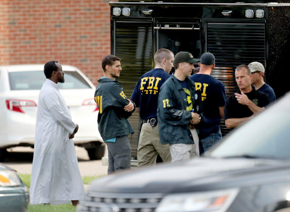 FILE - In this Aug. 15, 2017, file photo, law enforcement officials investigate the site of an explosion at the Dar Al-Farooq Islamic Center in Bloomington, Minn. Michael Hari, 49, of Clarence, Illinois, is the only one of three men accused in the attack to go to trial. Two Illinois men who pleaded guilty to a 2017 bombing of a Minnesota mosque testified that the group's alleged ringleader, Michael Hari, recruited them for an unspecified job and didn't fill them in on his plan until they neared their target. (David Joles/Star Tribune via AP, File)