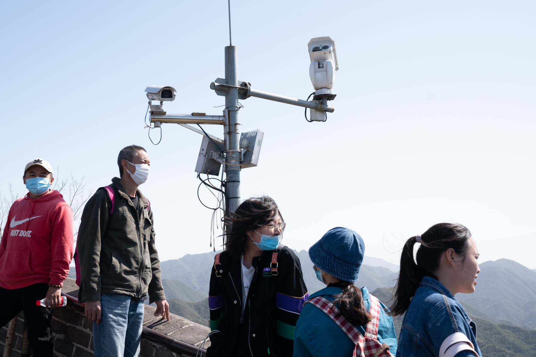 Visitors stand near surveillance cameras at the Badaling section of the Great Wall in Beijing, China, on Oct. 1, 2020.