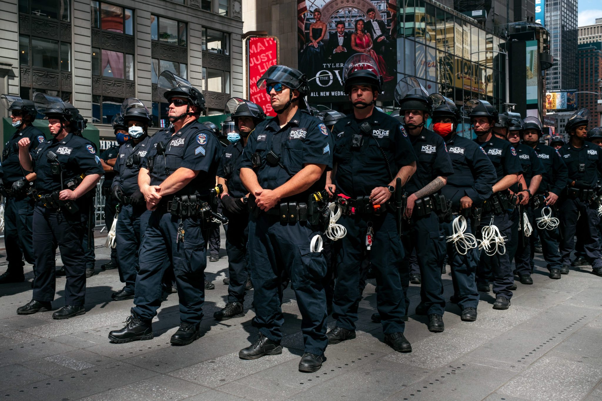 NEW YORK, NY - JUNE 01: NYPD officers stand in formation as nearby demonstrators hold a rally in Times Square denouncing racism in law enforcement and the May 25 killing of George Floyd while in the custody of Minneapolis, on June 1, 2020 in New York City. Days of protest, sometimes violent, have followed in many cities across the country. (Photo by Scott Heins/Getty Images)
