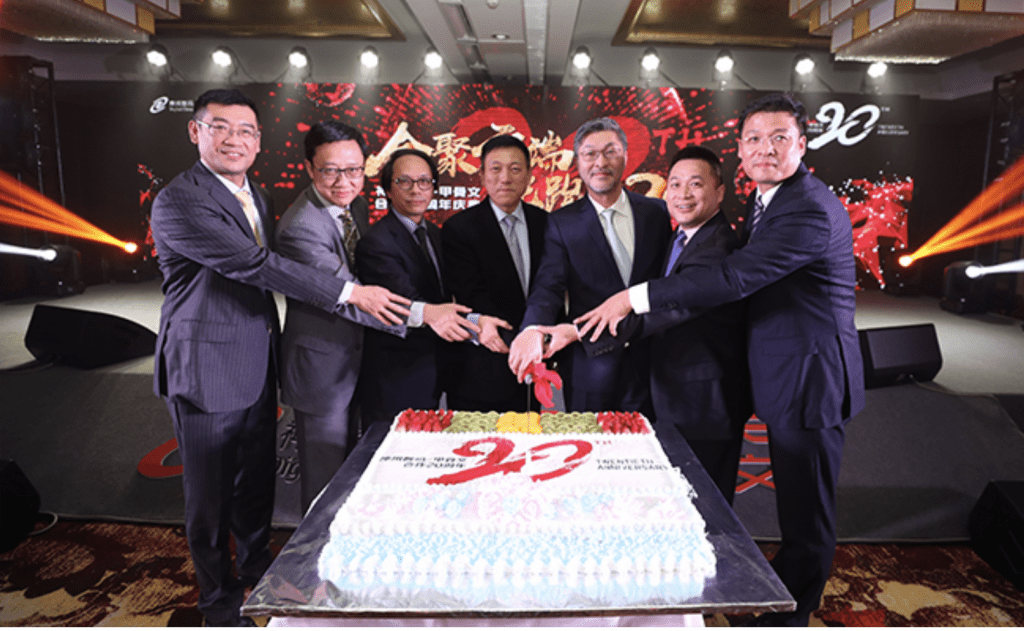 It shows a celebration held to commemorate 20 years of cooperation between the two companies that comes up in the story.