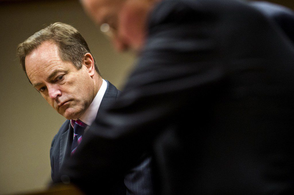 Special Prosecutor Todd Flood looks over as former Flint Emergency Manager Gerald Ambrose works with his attorney in Genesee District Court, in Flint, Mich., on Thursday, Jan. 25, 2018, to waive the preliminary examination in the prosecution against him related to the Flint water crisis. (Jake May /The Flint Journal-MLive.com via AP)
