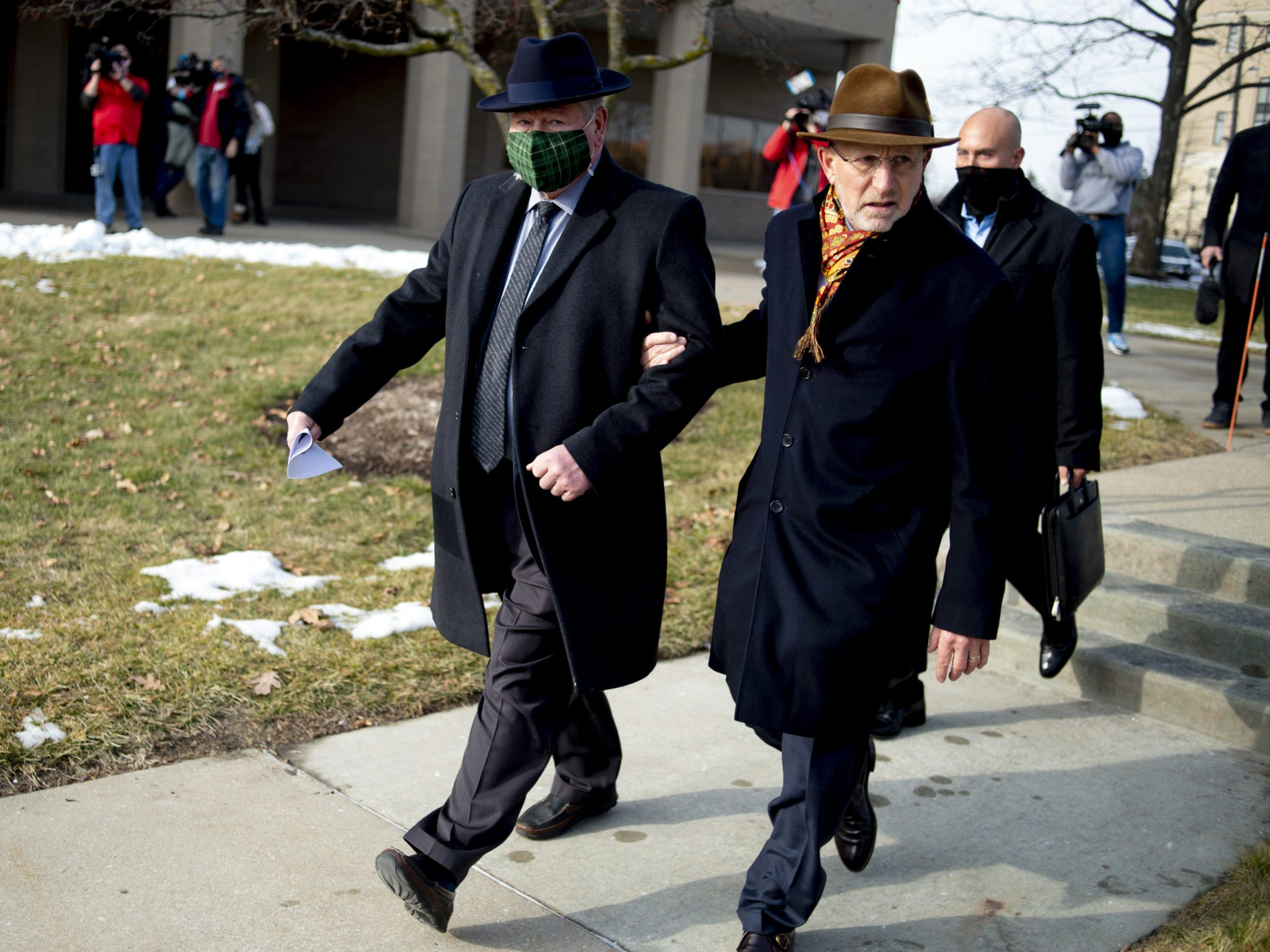 Attorney Randall Levine, right, walks arm-in-arm with Richard Baird, former transformation manager and senior adviser to former Michigan Gov. Rick Snyder, after a video arraignment on charges related to the Flint water crisis, Thursday, Jan. 14, 2021 at the Genesee County Jail in downtown Flint, Mich. Baird faces four felony counts, including perjury, official misconduct in office, obstruction of justice and extortion. (Jake May/The Flint Journal via AP)