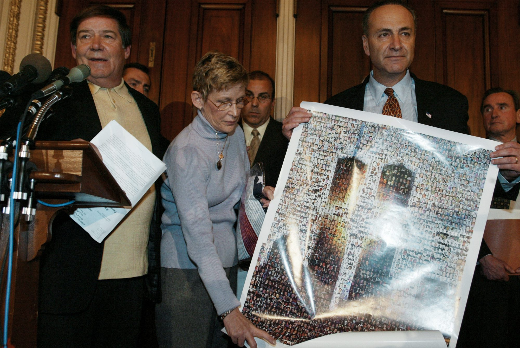 Bill Doyle, left, and Joan Molinaro, center, both from Staten Island, N.Y., parents of victims, present a poster of the World Trade Center bearing photographs of all the victims of the Sept. 11 terrorist attacks to Senator Charles Schumer, D-N.Y., during a news conference on terrorist financing on Capitol Hill Wednesday, March 19, 2003. Schumer said that new documents in possession by the Justice Department linking some of Saudi Arabia's most influential families to Al Qaeda should be made available tohelp victims' families prosecute those responsible for the Sept. 11 tragedy. Man rear center is John D'Amato, and rear right is Ronald Motley, attorney for the Sept. 11 families of victims. (AP Photo/Charles Dharapak)