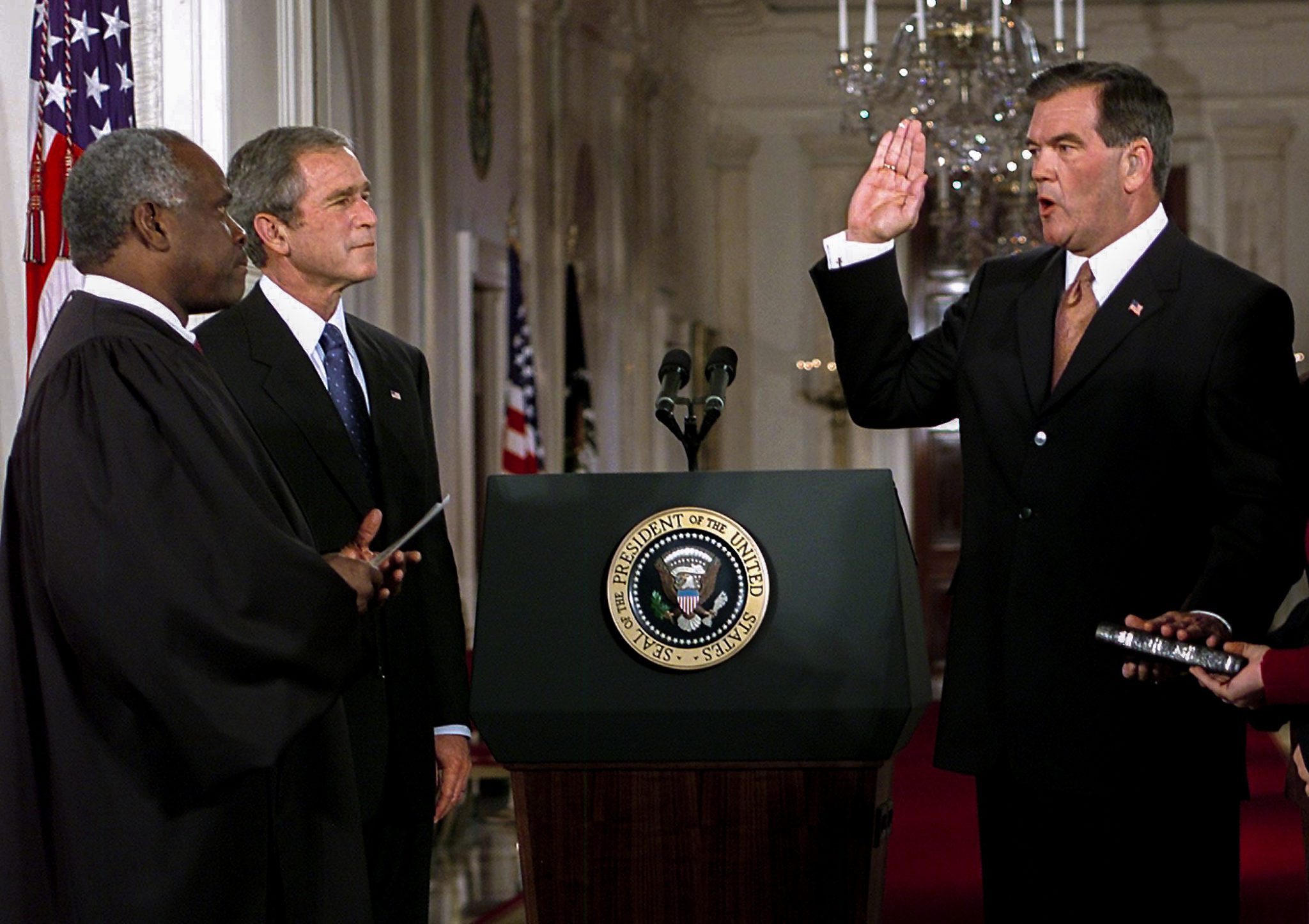 WASHINGTON, UNITED STATES:  Former Pennsylvania governor Tom Ridge (R) is sworn-in as Director of the newly created Cabinet-level position of the Office of Homeland Security 08 October, 2001 by Supreme Court Justice Clarence Thomas (L) as US President George W. Bush watches in the East Room of the White House in Washington, DC. The new position was created by the president to deal with terrorism within US borders.   AFP Photo/Paul J. Richards (Photo credit should read PAUL J. RICHARDS/AFP via Getty Images)