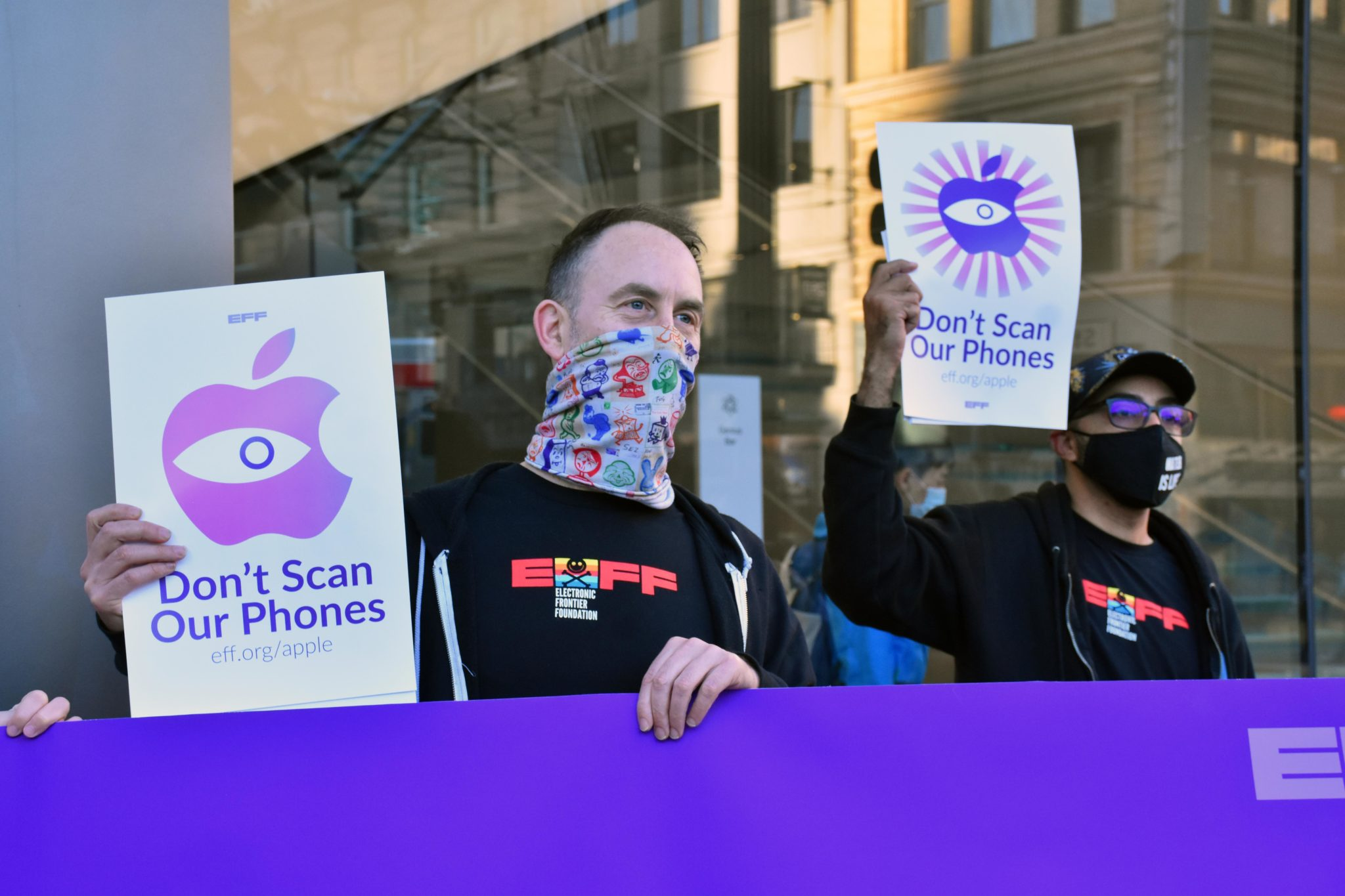 a man with a face mask on holds a banner reading dont scan our phones