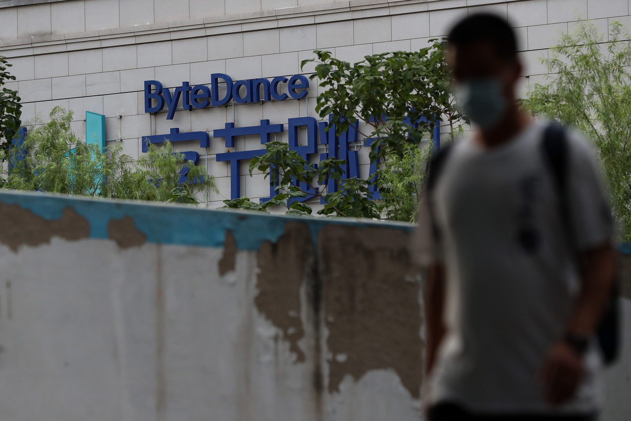 BEIJING, CHINA - AUGUST 04: A man wears protective mask as he walks past the ByteDance Ltd.'s office on August 04, 2020 in Beijing, China. TikTok is a Chinese video-sharing social networking service owned by a Beijing based internet technology company, ByteDance. The President of the United States Donald Trump is threatening and planning to ban the popular video sharing app TikTok from the US because of the security risk. Microsoft is interested in purchasing the TikTok platform in the United States. (Photo by Emmanuel Wong/Getty Images)